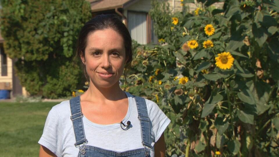 Une jeune femme souriant à la caméra devant des tournesols.