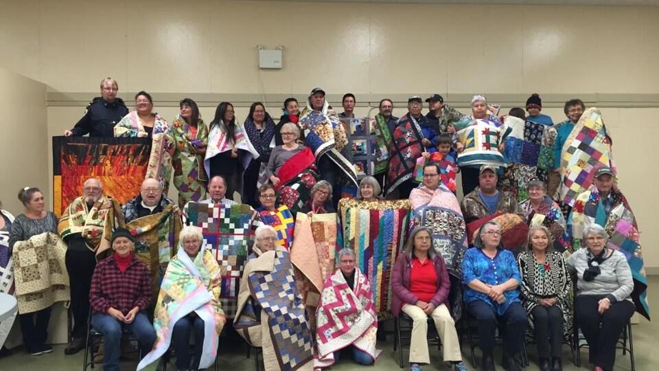 Un groupe de personnes enveloppées dans des couvertures colorées.