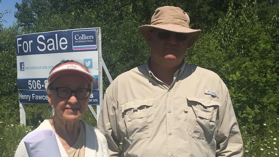 Veronica Stever et Kenneth Leet posent devant une pancarte « À vendre ».
