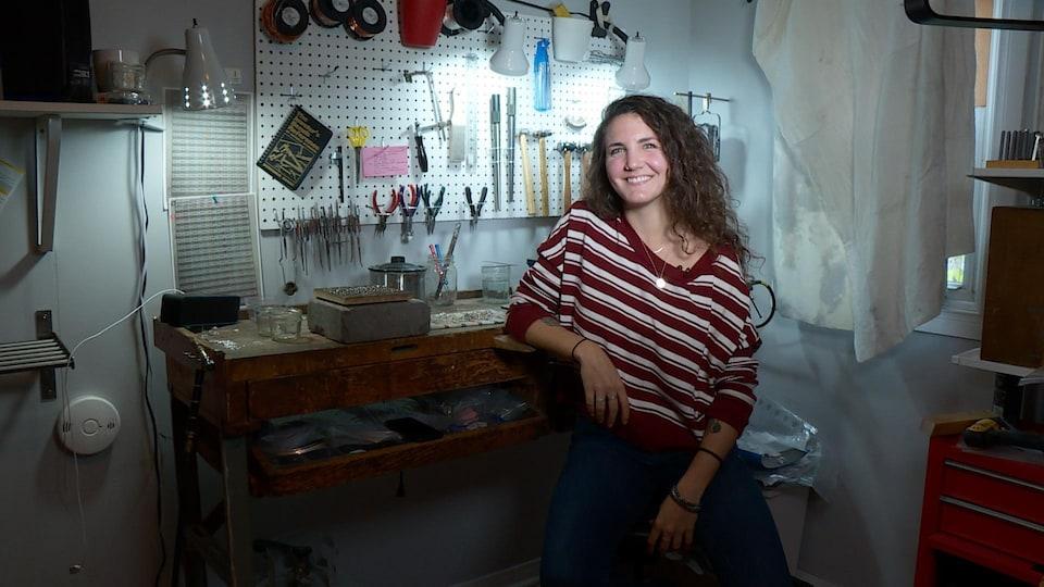 Une jeune femme se tient sur un tabouret devant son bureau où elle fabrique des bijoux.