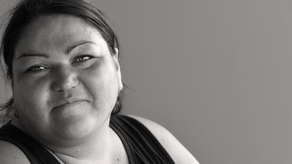 Une femme autochtone sourit. La photo est en noir et blanc.