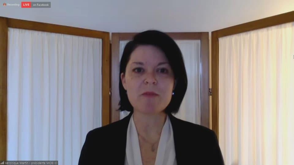 Une femme en conférence de presse via visioconférence.