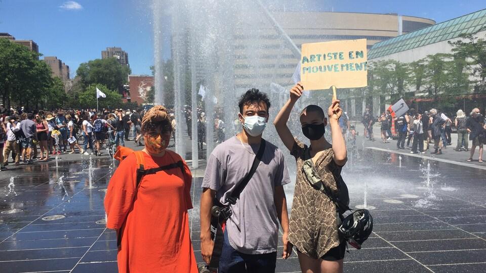Les trois personnes sont devant une fontaine et sont masquées.