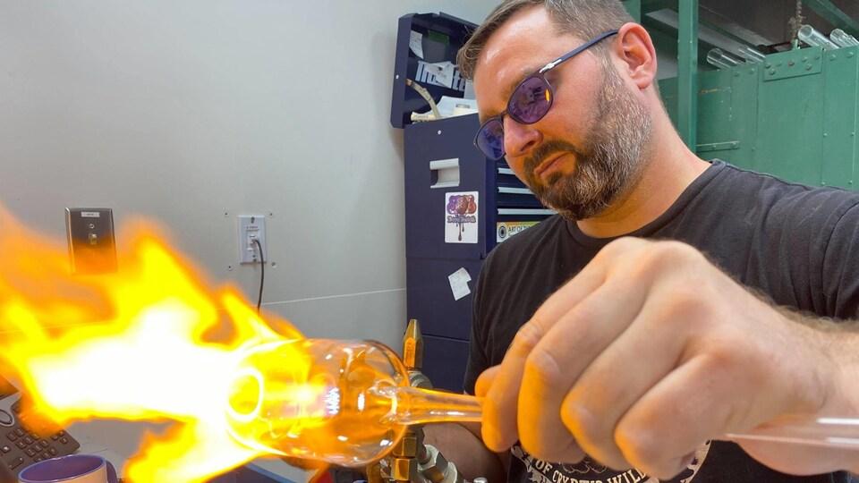 Cédric Ginart est souffleur de verre scientifique. Il fabrique à la demande des pièces pour les chercheurs à l'Université de Montréal. Il est entrain de travailler une pièce.