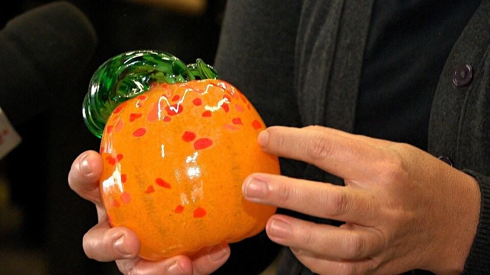 Une artisane tient entre ses mains une citrouille orange et verte en verre soufflé.