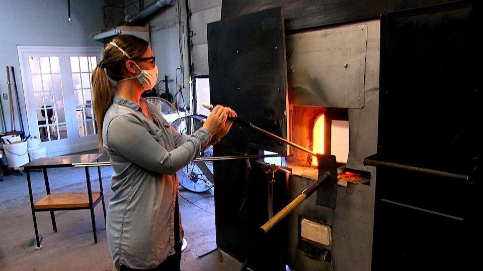 Une femme chauffe sa pièce de verre soufflé dans un four.