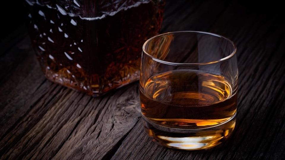 Un verre et une bouteille de whisky.