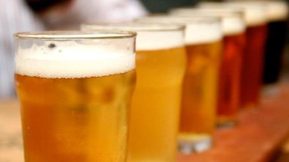Des verres de bières alignés sur un comptoir.