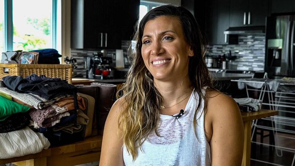Une jeune femme, assise dans son appartement, sourit lors d'une entrevue. Derrière elle, des vêtements sont empilés sur une table dans sa cuisine.
