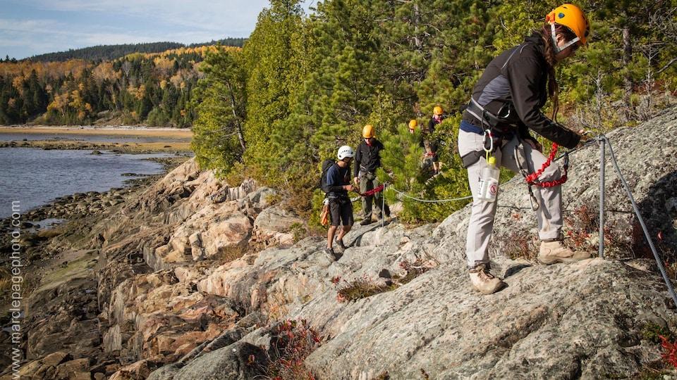 Des escaladeurs sur une paroi rocheuse, un lac et la forêt en arrière-plan.