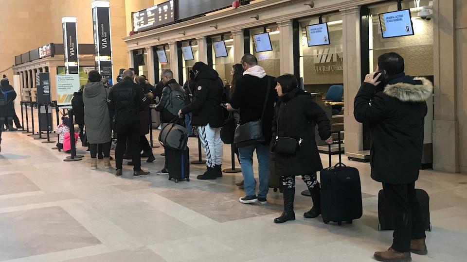 Des voyageurs attendent au guichet de Via Rail à la gare Union de Toronto.