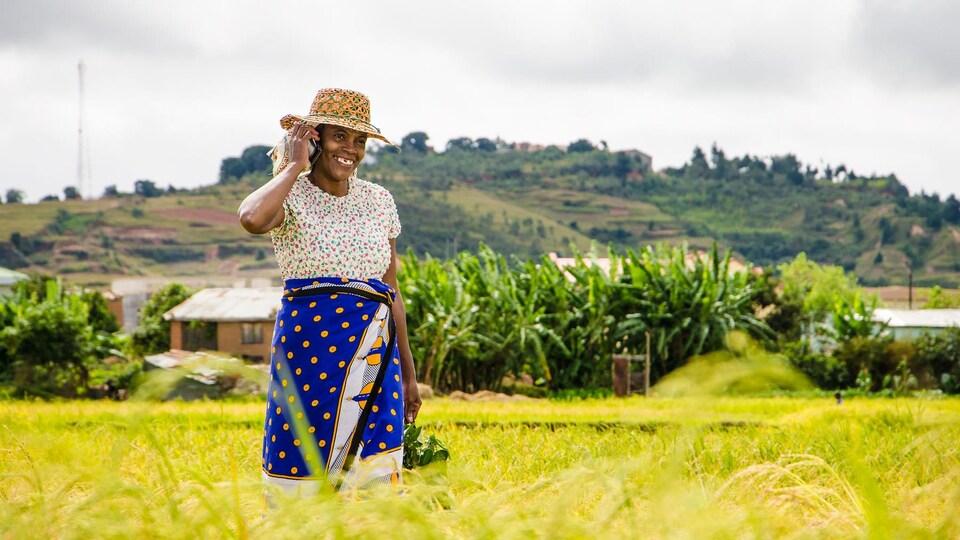 Une femme avec des habits colorés communique à l'aide d'un téléphone cellulaire dans un champ de Madagascar.