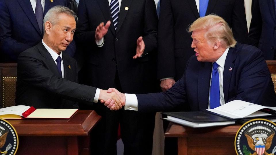 Le vice-premier ministre chinois Liu He et le président des États-Unis Donald Trump se serrent la main.