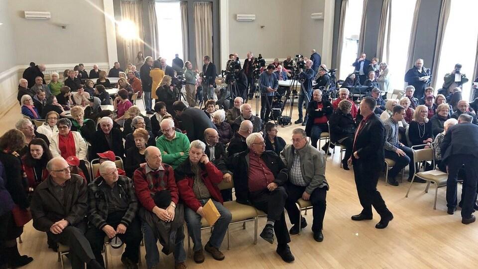 Plusieurs dizaines de personnes sont assises dans la salle