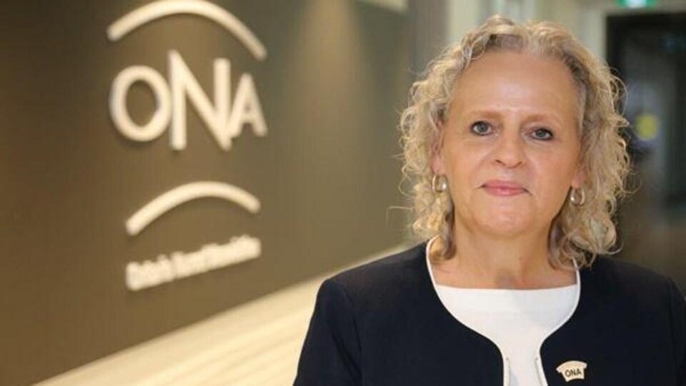 Le portrait d'une femme devant le logo de son association.