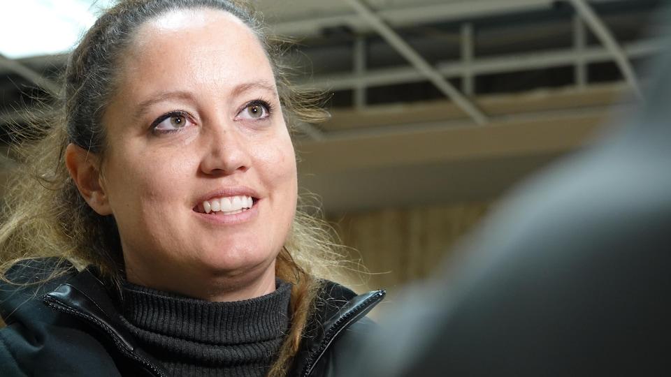 Portrait d'une femme qui parle à la caméra.