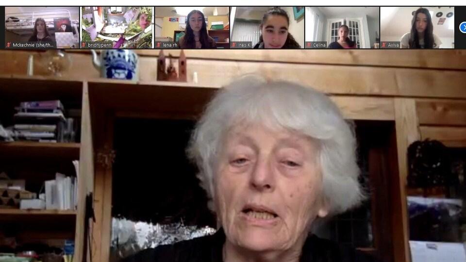 Une dame âgée aux cheveux blancs courts est au centre d'un écran et en haut de cet écran, il y a de petites fenêtres des jeunes filles qui écoutent cette dame en ligne.