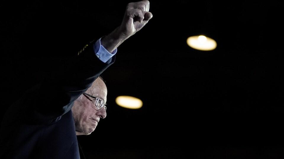 Le candidat démocrate à la présidence, le sénateur Bernie Sanders, lève le poing en arrivant sur scène.