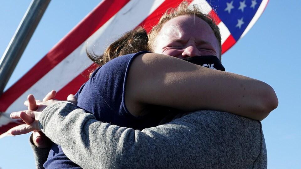 Deux personnes se serrent dans leurs bras, le drapeau américain en arrière plan.