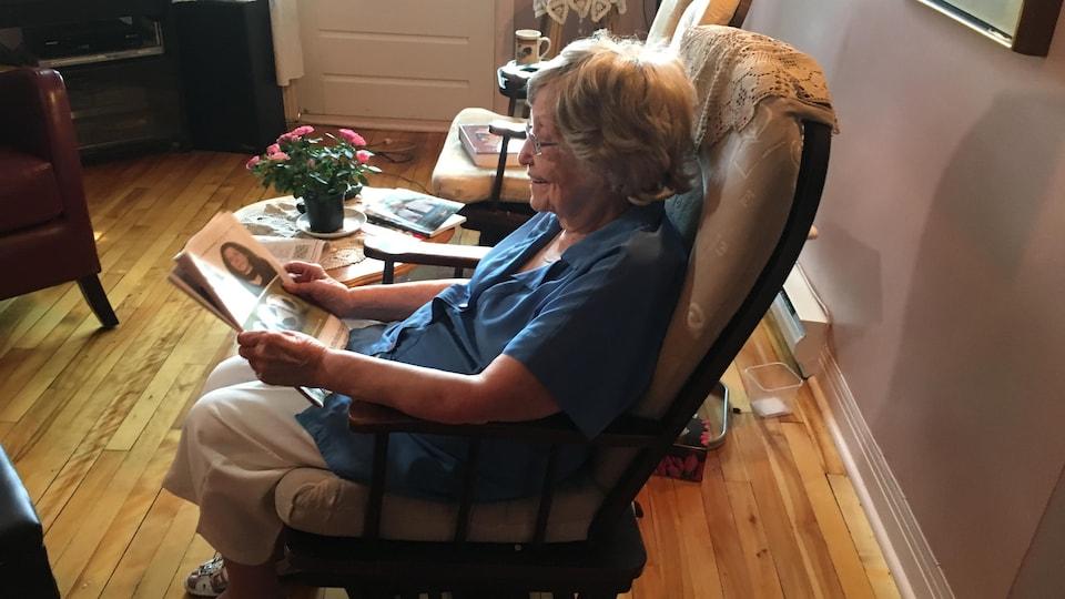 Mme Simoneau lit le journal dans son salon.