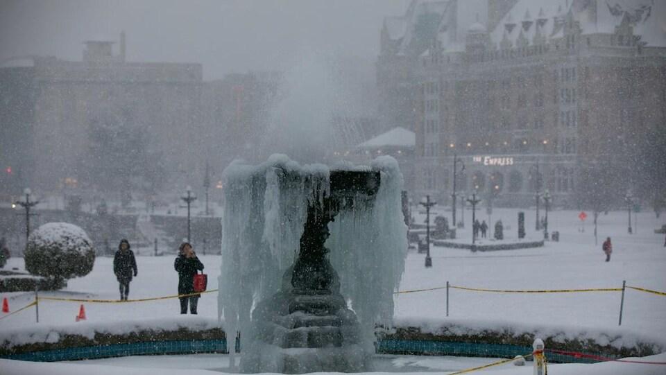 Un fontaine presque complètement glacée, une personne la prend un photo avec son cellulaire, et on voir un bâtiment en arrière-plan, flou en raison de la neige qui tombe.