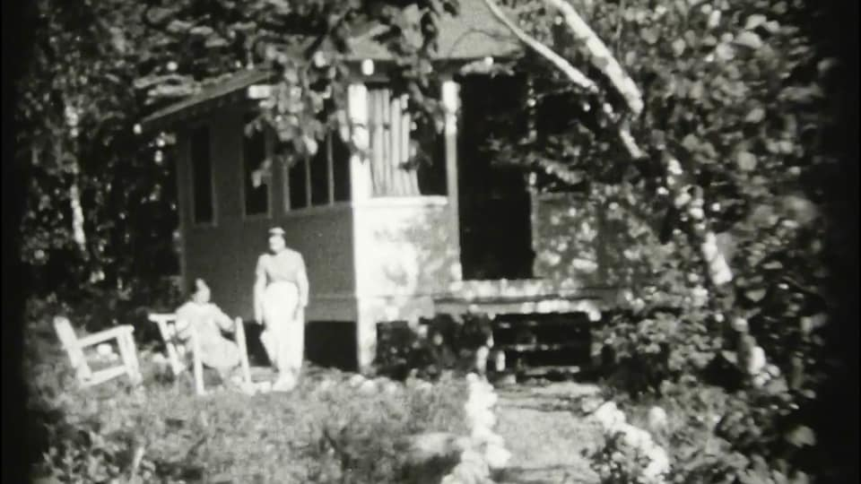 Image d'archive d'un chalet à côté duquel deux personnes se trouvent.