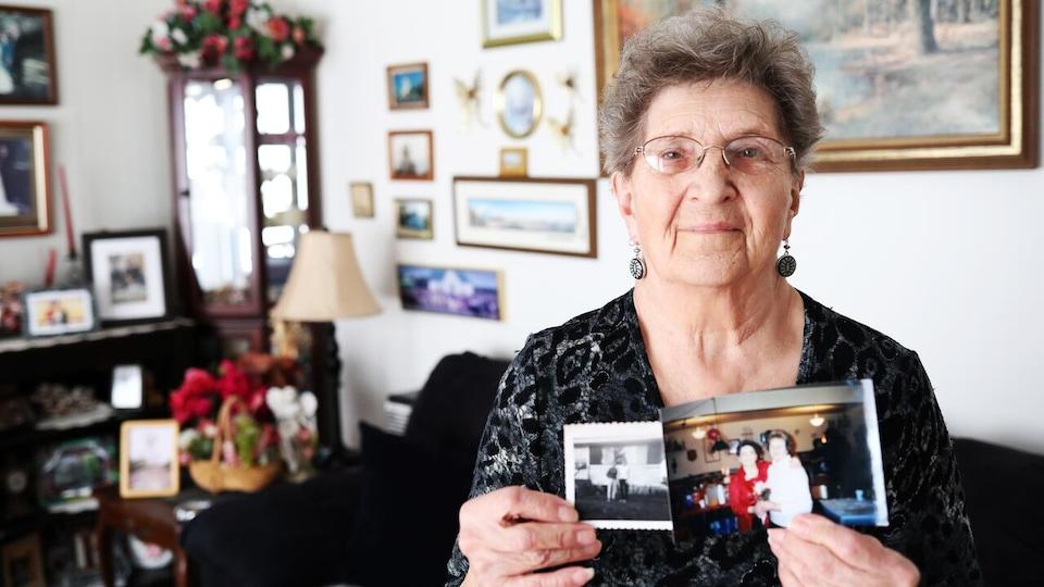 Victoria Kryczak, qui porte des lunettes, sourit à la caméra en montrant deux photos d'elle et de son amie Kathleen Wallace.