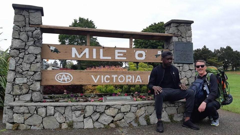 deux hommes posant devant le panneau Mile 0 Victoria