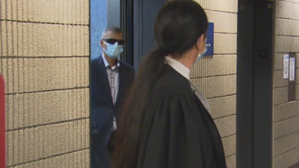 Victorio Reno Pereira, portant un masque et des lunettes de soleil, sort d'une salle au palais de justice, tandis qu'on voit son avocate dans le corridor.