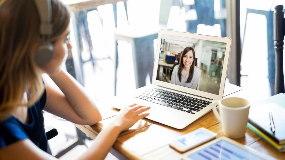 Une femme portant des écouteurs discute avec une autre femme par vidéoconférence sur un ordinateur.