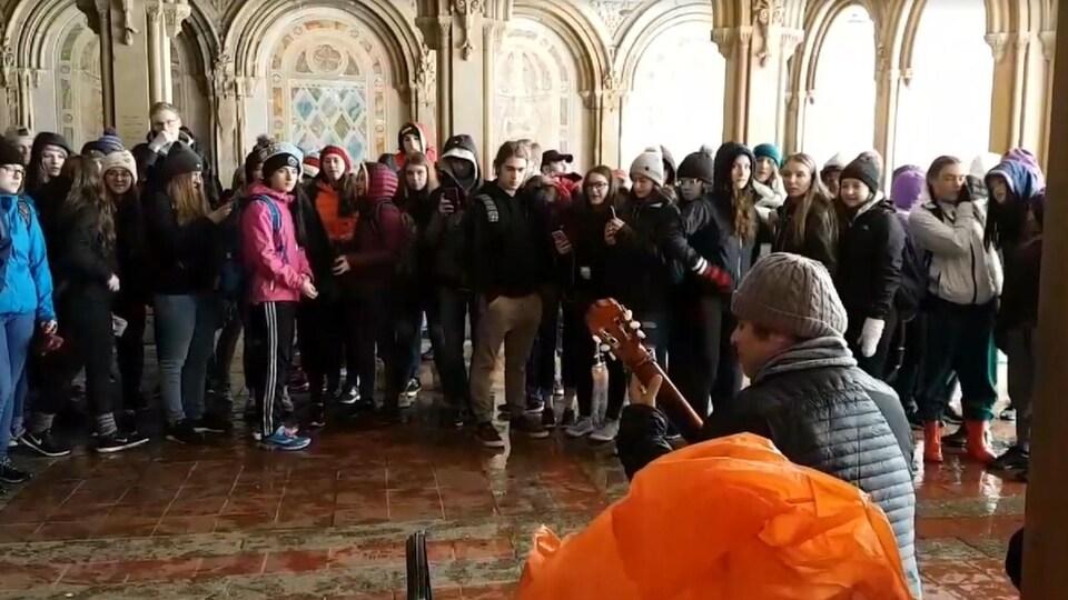 Des adolescents écoutent un musicien sous un pont à Central Park.