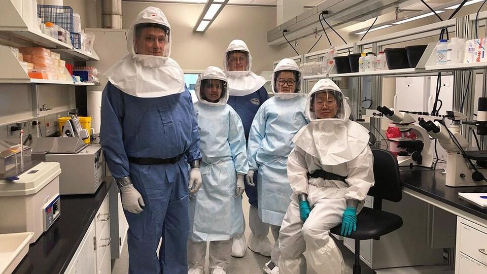 Des travailleurs dans un laboratoire posent pour le photographe avec des habits pour se protéger.