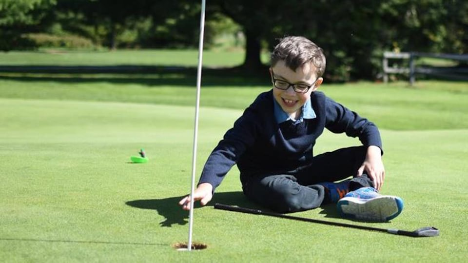 Un petit garçon qui porte des lunettes est assis dans l'herbe. Il regarde le huitième trou lors d'un tournoi de golf.