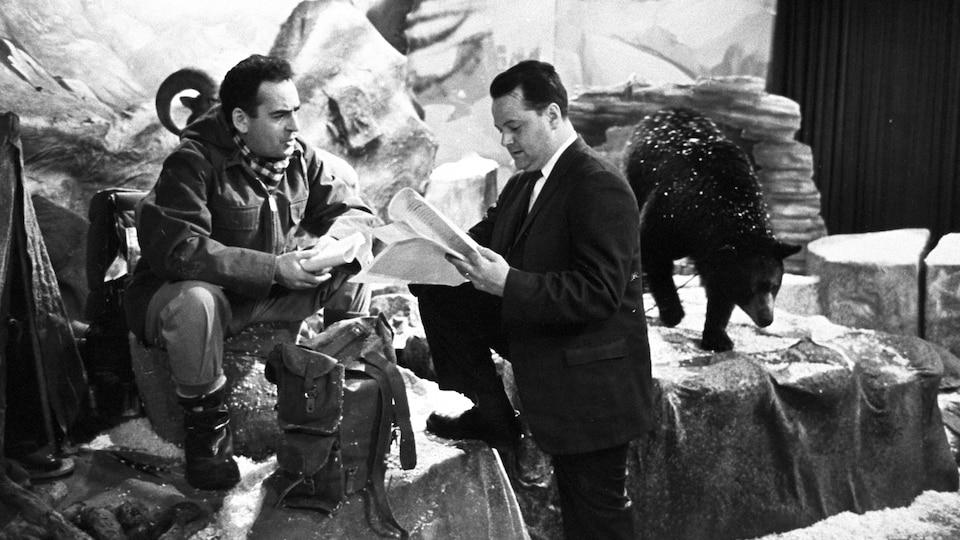 L'animateur Guy Provost discute avec le réalisateur Michel Demers qui consulte son plan de l'émission, sans se préoccuper de l'ourson qui se promène derrière lui.