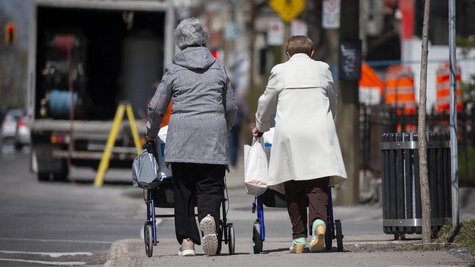 Deux personnes âgées marchent dans le centre-ville de Montréal.