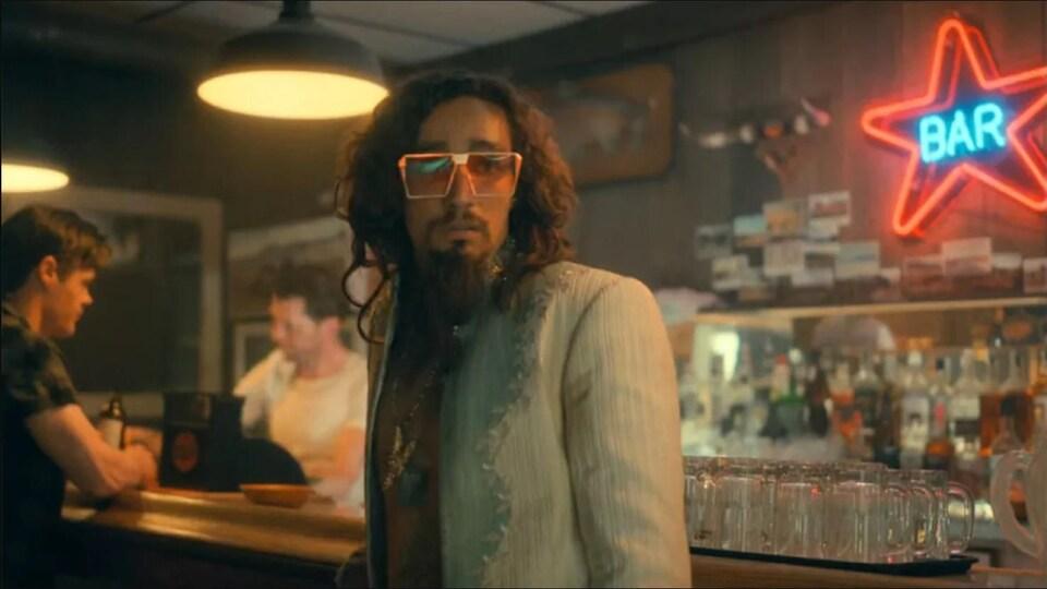 Un homme avec de larges lunettes orange regarde devant lui, accoté sur un comptoir de bar.