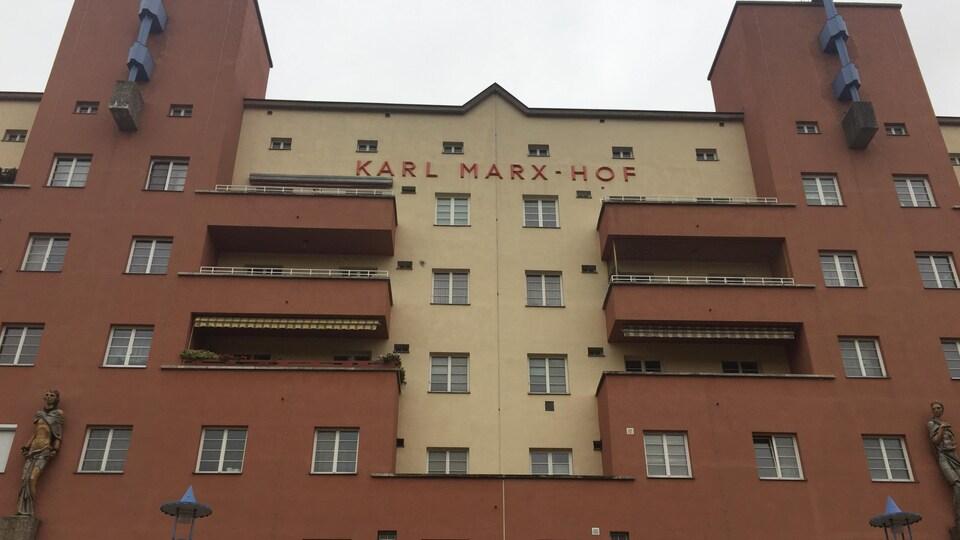 Un immeuble de logement des années 20 avec des statues.