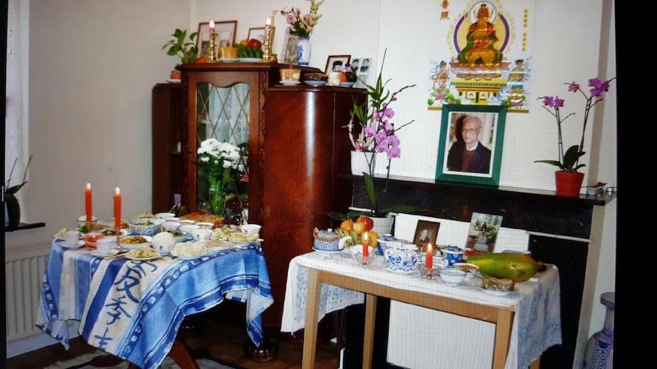 Deux tables sur lesquelles sont disposés des fleurs, des bougies allumées, des fruits et d'autres aliments. On voit également la photo d'un homme et une armoire.