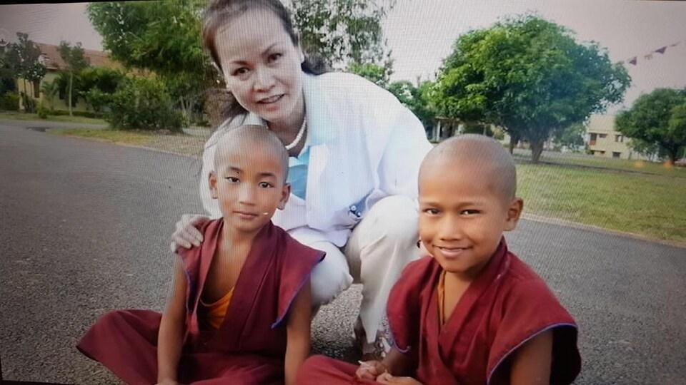 Une femme accroupie entre deux enfants vêtus en tenue traditionnelle.