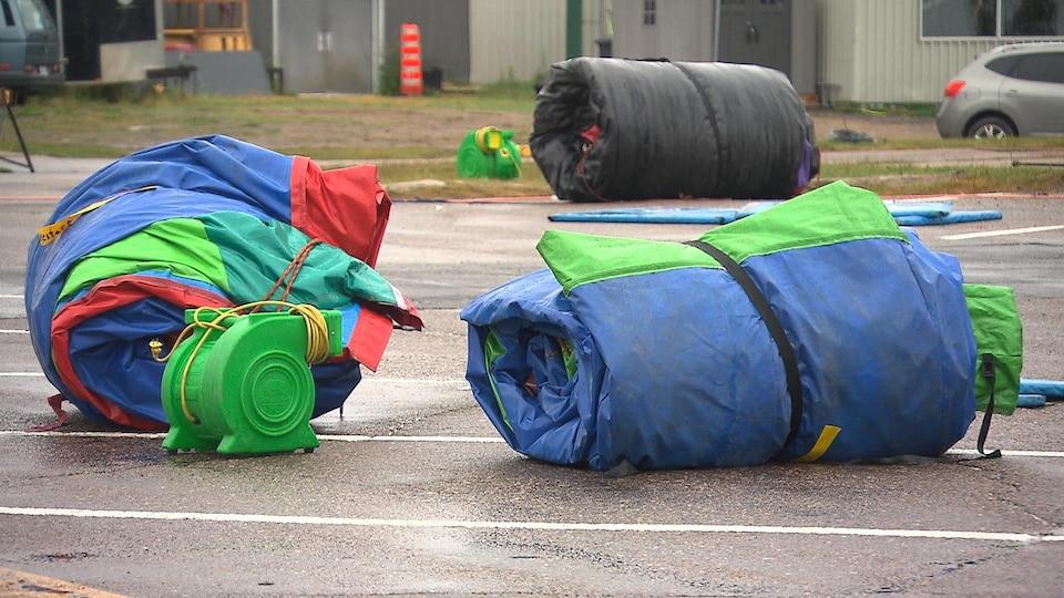 Deux jeux gonflables dégonflés et roulés sur l'asphalte.