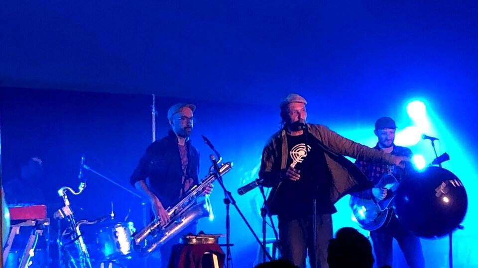 Bernard Adamus est entouré d'un saxophiste et d'un guitariste.