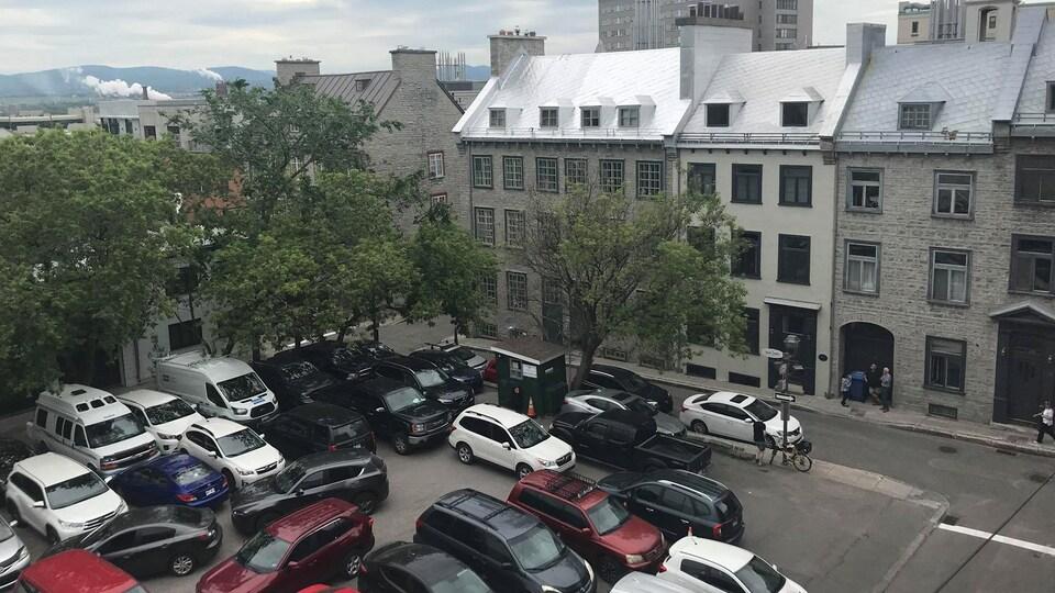 Au premier plan, on peut voir des dizaines de voitures stationnées. Ensuite, on peut voir des édifices de trois étages et des lucarnes.