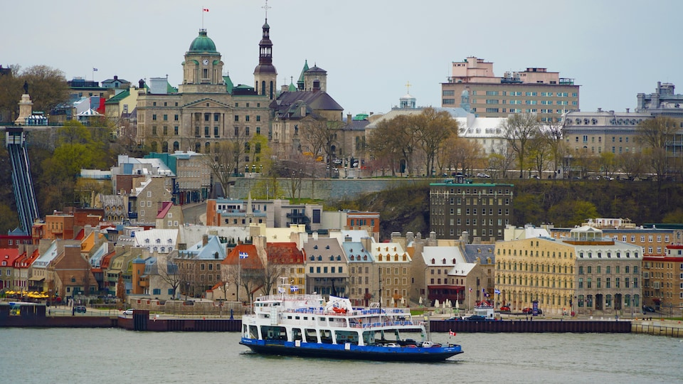 Le Vieux-Québec qui surplombe le fleuve vu à partir la rive sud avec le traversier qui arrive tranquillement au quai.