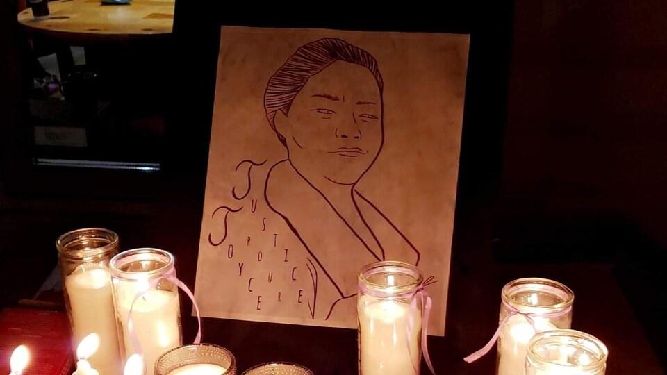 Des chandelles sont placées devant un dessin de femme.