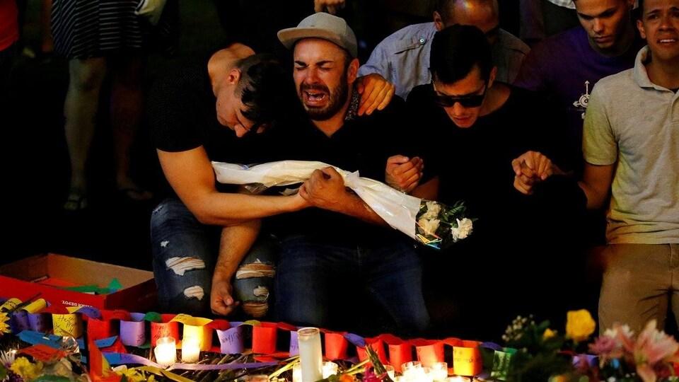 Quatre hommes agenouillés se tiennent la main et pleurent devant des chandelles