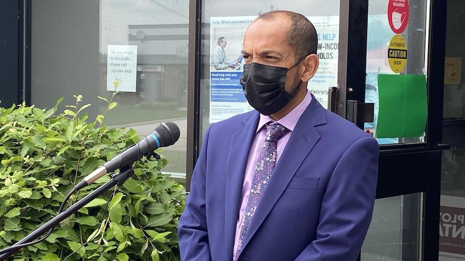 Le Dr Vikesh Maraj est devant un micro et un pupitre. Il arbore un masque chirurgical.