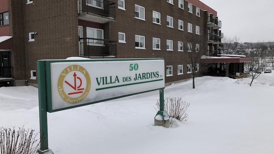 Façade de l'édifice et affiche de la Villa Des Jardins.