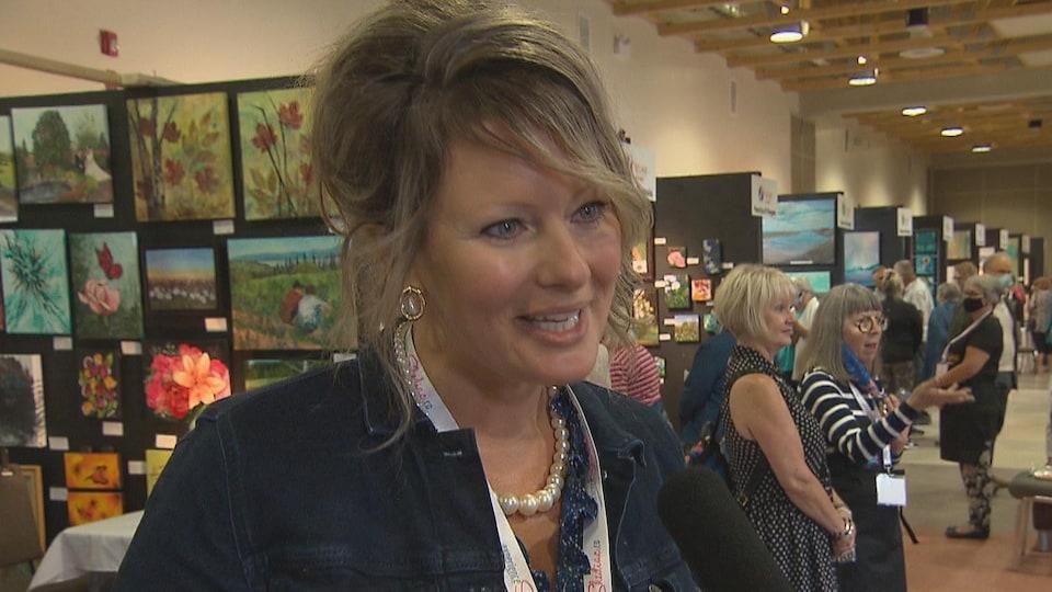 Une femme souriante devant des présentoirs où sont affichés des tableaux d'artistes.