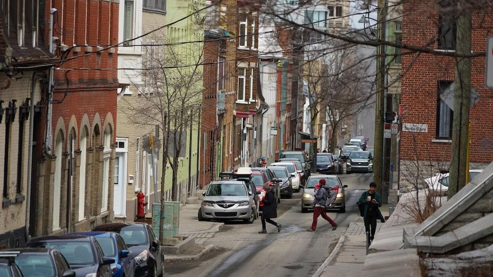Des piétons circulent dans les rues de la haute-ville, au printemps.