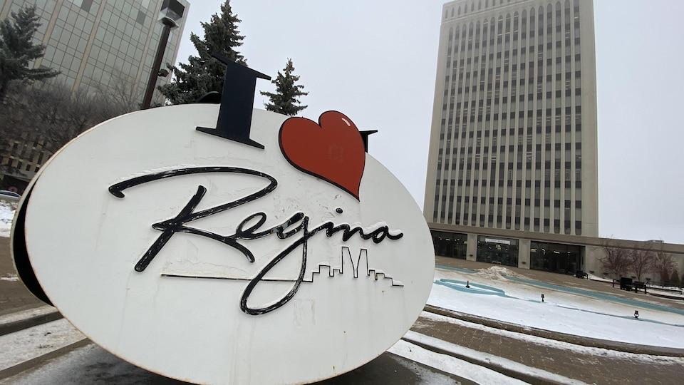 Gros plan sur une affiche « J'aime Regina », devant l'hôtel de ville.